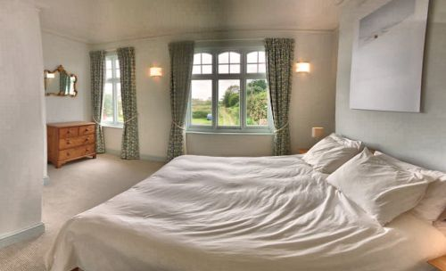 The Front Bedroom has a sea view and a kingsize bed.