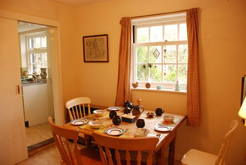 The Dining Room at Lamorna Cottage with sliding door to Kitchen.