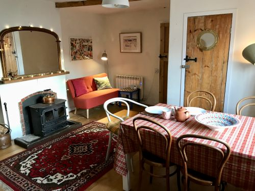 The dining room has a wood burning stove and sofa