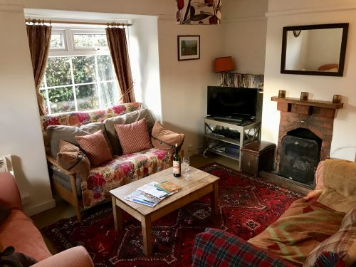 The living room has three two-seater sofas, and an open fire.