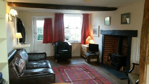 Sitting room area with inglenook, beams, wood-burner feature, TV, DVD player, CD player and board games.
